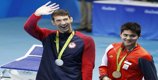 Silver medallist USA's Michael Phelps (L) waves nex to gold medallist Singapore's Schooling Joseph during the medal ceremony of the Men's 100m Butterfly Final during the swimming event at the Rio 2016 Olympic Games at the Olympic Aquatics Stadium in Rio de Janeiro on August 12, 2016. / AFP / Odd Andersen (Photo credit should read ODD ANDERSEN/AFP/Getty Images)